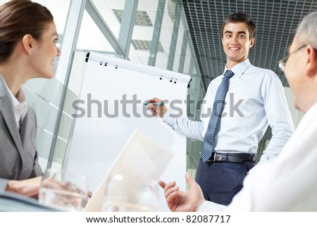 Smiling business man presenting new project to his partners on a whiteboard