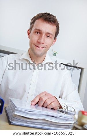 Smiling business man sitting at his desk in the office
