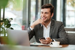 Smiling business man sitting by the table in cafe with laptop computer and smartphone while looking away