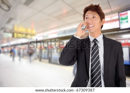 Smiling business man using cellphone in station.