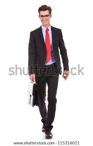 smiling business man wearing glasses is walking with a briefcase