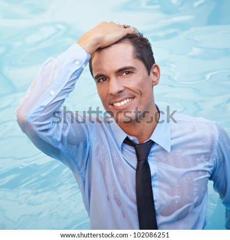 Smiling business man with wet clothes in blue water