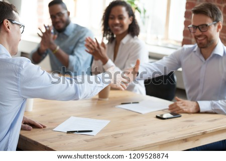 Smiling business partners shake hands after successful negotiations in office, excited male workers handshake greeting with employment, happy employees get acquainted at meeting. Partnership concept