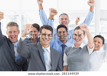 Smiling business people cheering in office