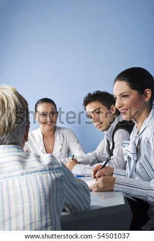Smiling business people having a meeting and they discussion together on blue background