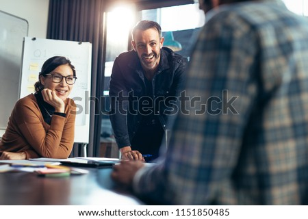 Smiling business people paying attention to colleagues discussion in meeting room. Happy and positive business team meeting in conference room.