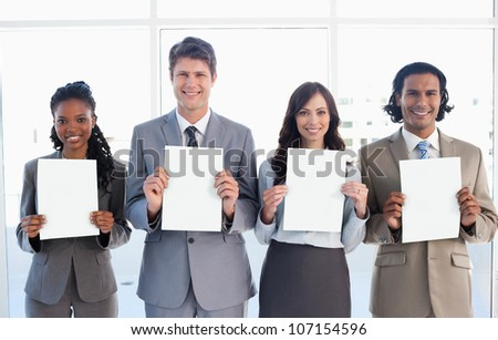 Smiling business people standing in front of a window while showing blank sheets