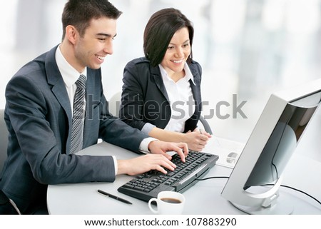 Smiling business people with computer in board room