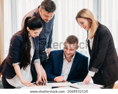 smiling business team looking at documents. successful company growth. positive financial results. men and women standing around their boss in office workspace #1068932150