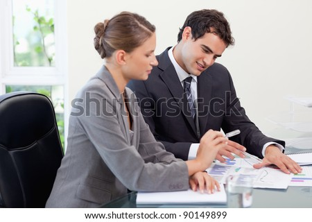 Smiling business team studying statistics in a meeting room