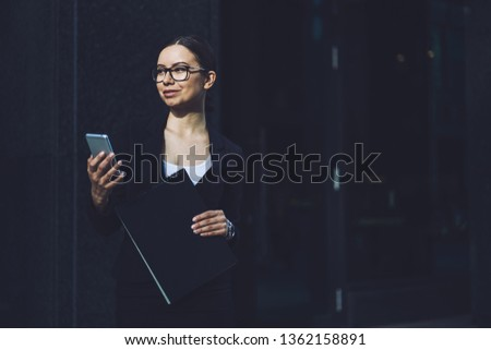 Smiling business woman in eyewear for vision correction holding mobile phone in hand using 4g connection for communicate with partners via application, concept of professionalism and technology