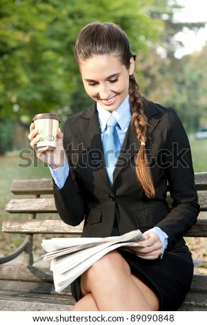 smiling business woman relaxing in park, reading newspaper and drinking coffee