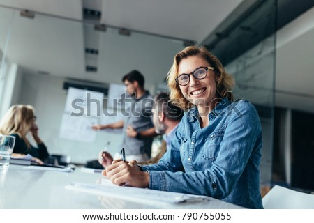 Smiling business woman sitting in conference room during presentation. Caucasian woman sitting in board room.