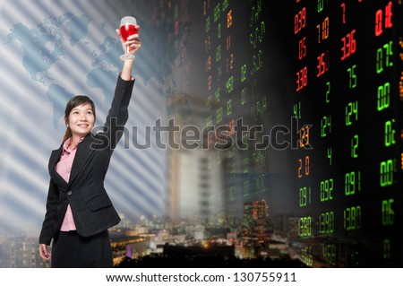Smiling business woman standing holding a glass of champagne. over stock exchange background