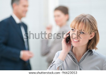 Smiling business woman talking on mobile phone at office