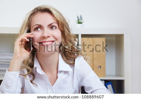 Smiling business woman using smartphone to make a call