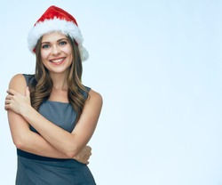 smiling business woman wearing christmas hat standing against white background with crossed arms. isolated portrait.