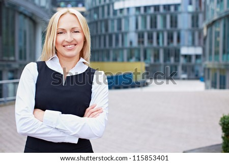 Smiling business woman with her arms crossed outside the office - stock photo