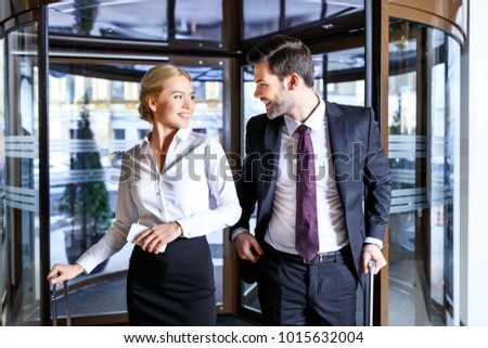 smiling businessman and businesswoman entering hotel and looking at each other #1015632004