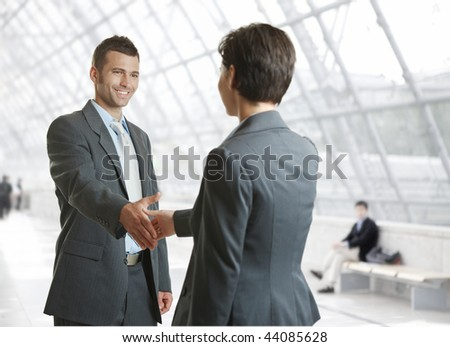 Smiling businessman and businesswoman shaking hands in hallway.
