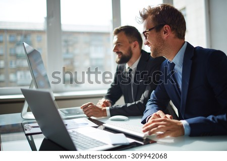 Smiling businessman and his colleague looking at computer monitor at meeting #309942068