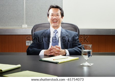 Smiling businessman at conference table