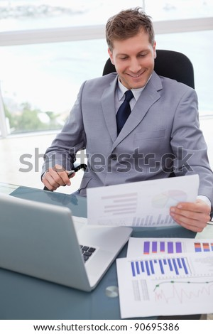 Smiling businessman at his desk looking at market research results