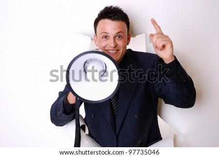 smiling businessman break through a paper wall - stock photo