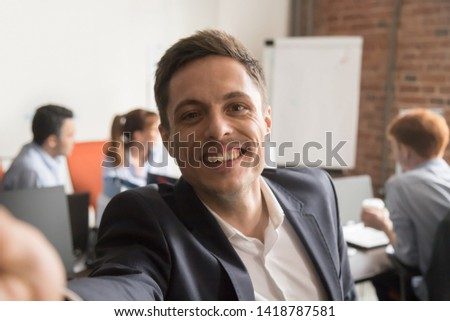 Smiling businessman company director in suit looking at camera make conference video call e-coaching perform training online, record blog webinar communicate with client standing in shared office room