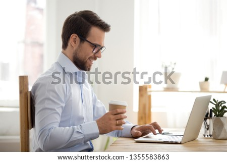 Smiling businessman drinking coffee and using laptop at workplace, confident with cardboard cup, typing on keyboard, looking at screen, reading business email, chatting with friends during break