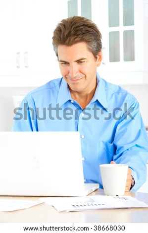 Smiling businessman drinking coffee and working with laptop at home