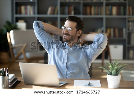 Smiling businessman freelancer wearing glasses leaning back in chair with hands behind head, happy satisfied young man dreaming about good future, new opportunities, visualizing success