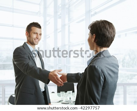 Smiling businessman greeting businesswoman with handshake before meeting.