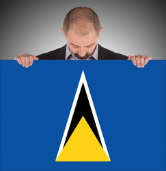 Smiling businessman holding a big card, flag of Saint Lucia