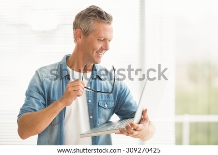 Smiling businessman holding a laptop at the office