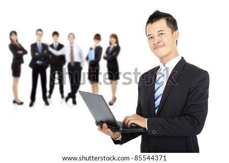 smiling businessman holding laptop and successful business team