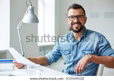 Smiling businessman in denim shirt and eyeglasses looking at camera in office Foto d'archivio ©