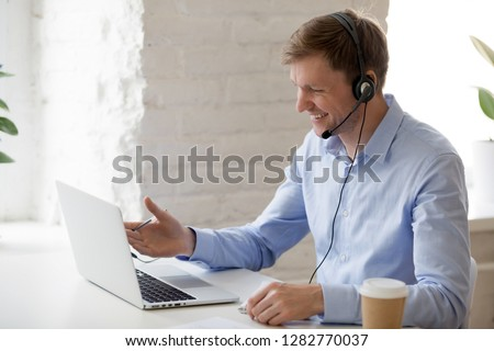 Smiling businessman in headphones looking at laptop screen, watching good webinar, consulting client, distance learning languages, making notes, happy man participating online conference