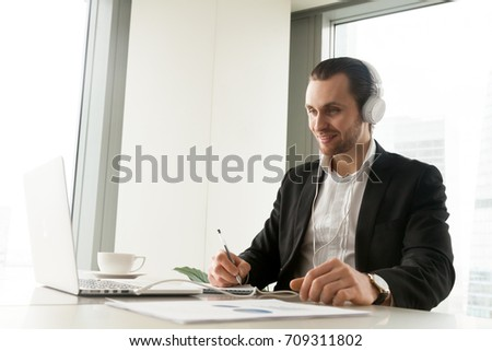 Smiling businessman in headphones taking notes in front of laptop at workplace. Friendly young manager participating in online meeting or conference, remote job interview, learning foreign languages.