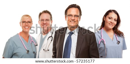 Smiling Businessman in Suite and Tie While Male and Female Doctors and Nurses Stand Behind Isolated on a White Background.