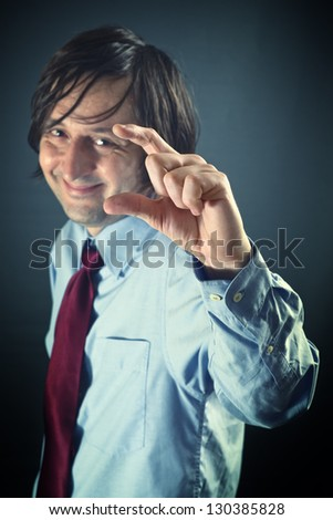 Smiling businessman is mocking, showing a small sign with his fingers. Mock, gibe, jeer, ridicule concept.