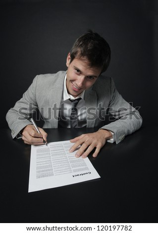 Smiling businessman is signing a contract