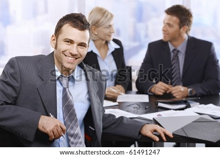 Smiling businessman looking at camera sitting at meeting table, coworkers in background.?