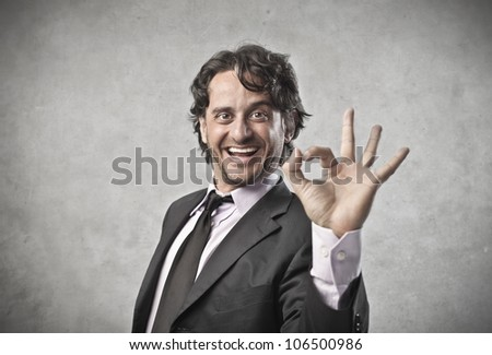 Smiling businessman making an ok sign with his hand