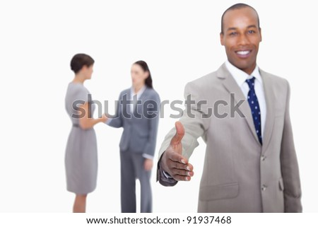 Smiling businessman offering his hand with hand shaking colleagues behind him against a white background