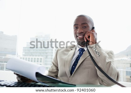 Smiling businessman on the phone while reading a document in his office