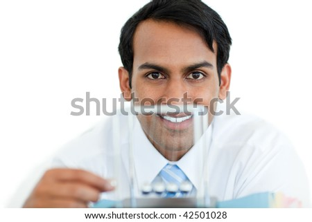 Smiling businessman playing with kinetic balls at work