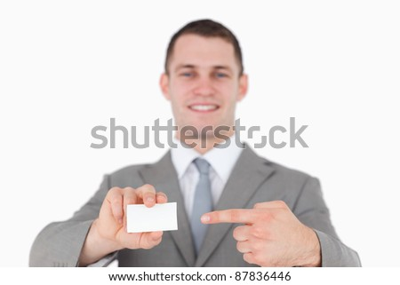 Smiling businessman pointing at a blank business card against a white background