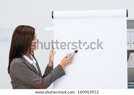 Smiling businessman pointing to a blank flipchart with copyspace for your text as she does a business presentation in the office