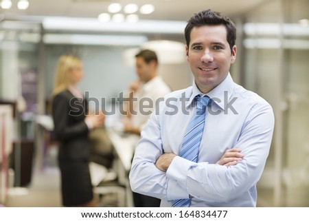 Smiling Businessman posing while colleagues talking together in office